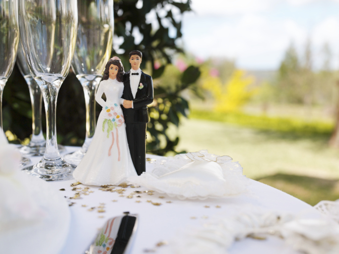 Bride and groom figurine on table by champagne flutes